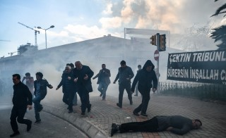 A man lies on the ground as others run as Turkish anti-riot police officers use tear gas to disperse supporters in front of the headquarters of the Turkish daily newspaper Zaman in Istanbul on March 5, 2016. Protests erupted after Turkish authorities seized the newspaper's headquarters in a midnight raid. Turkish authorities took control of the newspaper staunchly opposed to President Recep Tayyip Erdogan after using tear gas and water cannon to seize its headquarters in a dramatic raid that raised fresh alarm over declining media freedoms. Police fired the tear gas and water cannon just before midnight at a hundreds-strong crowd that had formed outside the headquarters of the Zaman daily in Istanbul following a court order issued earlier in the day. / AFP / OZAN KOSE        (Photo credit should read OZAN KOSE/AFP/Getty Images)