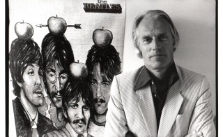 Legendary producer George Martin poses with poster of the Beatles in 1984. Photo by Rob Verhorst/Redferns via Getty Images