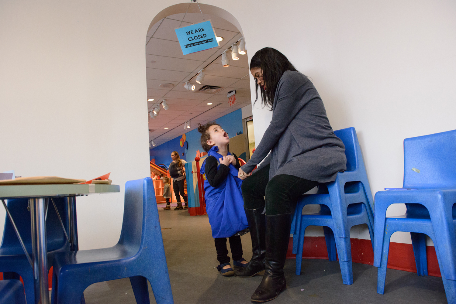 """Seven months pregnant, Vice President of Programs and Education at Brooklyn Children's Museum Petrushka Bazin Larsen fixes her daughter, Ila Bazin Larsen's """"Elsa dress"""" while working on a stressful day when child care had fallen through."""