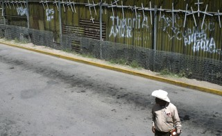 A man stands next to the wall that separates the Mexican city of Nogales Sonora and Nogales Arizona, in May 2010. Photo by Alonso Castillo/Reuters