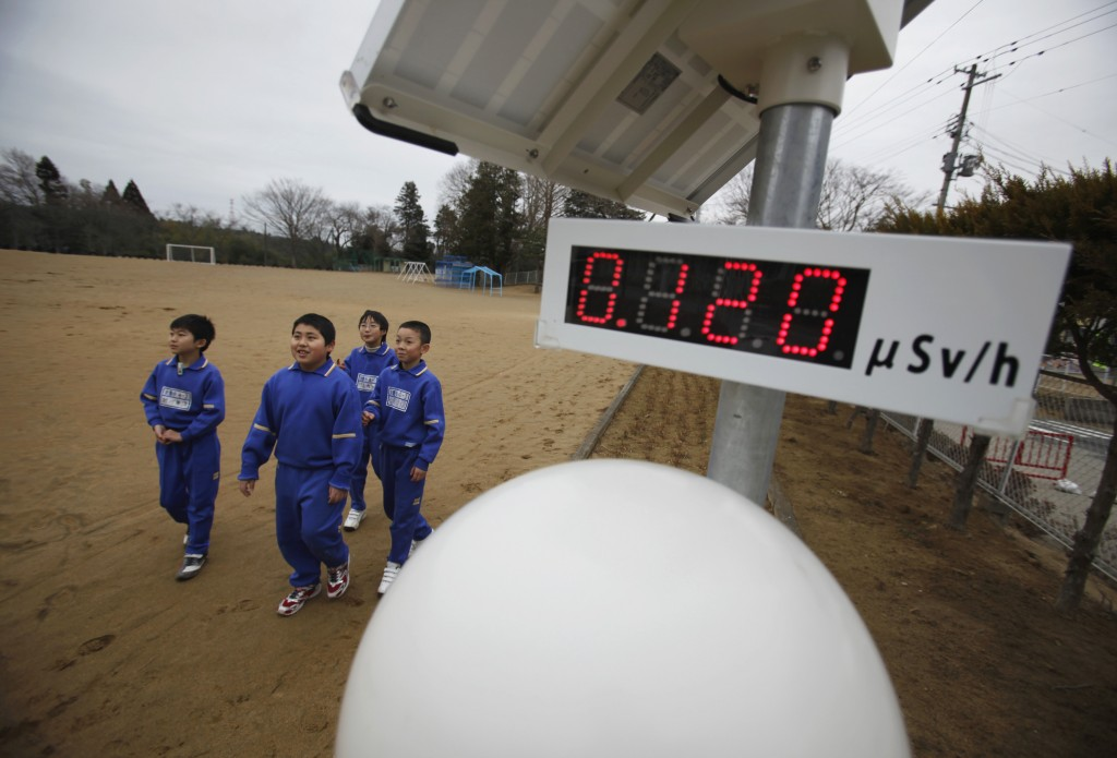 Students walk near a geiger counter near Omika Elementary School, located 13 miles from the tsunami-crippled Fukushima Dai-ichi nuclear power plant. Photo by Toru Hanai/ Reuters