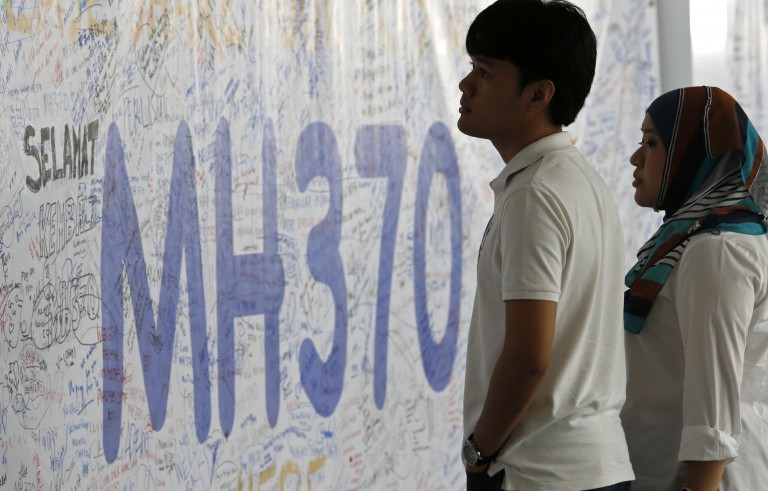 People look at a banner of well wishes for the passengers of the missing Malaysia Airlines MH370 plane at Kuala Lumpur International Airport in 2014. Photo by Edgar Su/Reuters