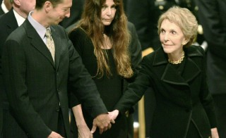 Nancy Reagan (right) reaches out to her son Ron Reagan Jr. (left) as her daughter Patti Davis looks on during the funeral for former President Ronald Reagan at the Washington National Cathedral in Washington, on June 11, 2004. Photo by Kevin Lamarque/Reuters