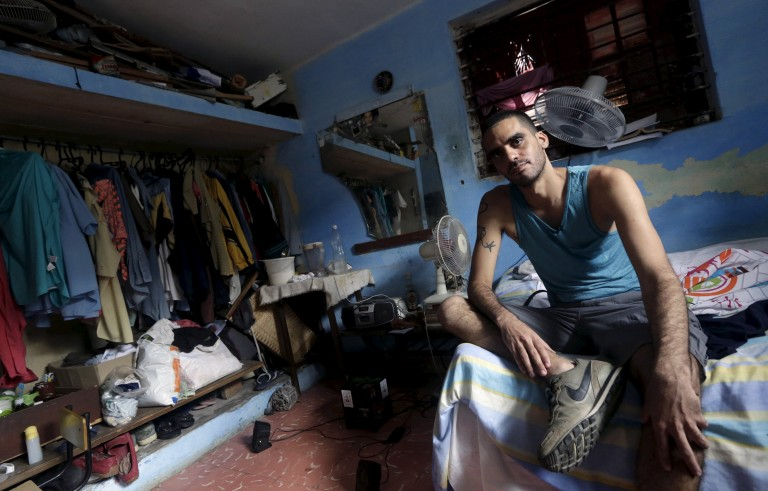 """Cuban graffiti artist Danilo Maldonado sits in his room in Havana October 20, 2015. Cuba released a graffiti artist known as """"El Sexto"""" on Tuesday, ten months after he was jailed for """"disrespect of the leaders of the revolution"""" over a satire of Fidel and Raul Castro. Amnesty International in late September had declared Danilo Maldonado, 32, the country's only prisoner of conscience, but added it was evaluating other cases. REUTERS/Enrique de la Osa - RTS5CI7"""