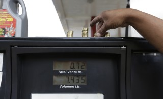 A gas station attendant piles up coins on top of a fuel dispenser at a gas station of state oil company Petroleos de Venezuela (PDVSA) before the government raised the price for fuel, in Caracas, February 16, 2016.  REUTERS/Marco Bello   - RTS95DB