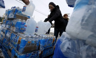 Volunteers distribute bottled water to help combat the effects of the crisis when the city's drinking water became contaminated with dangerously high levels of lead in Flint, Michigan, March 5, 2016. the latest lawsuit against over the crisis was launched on Thursday. Jim Young/Reuters RTS9GRU