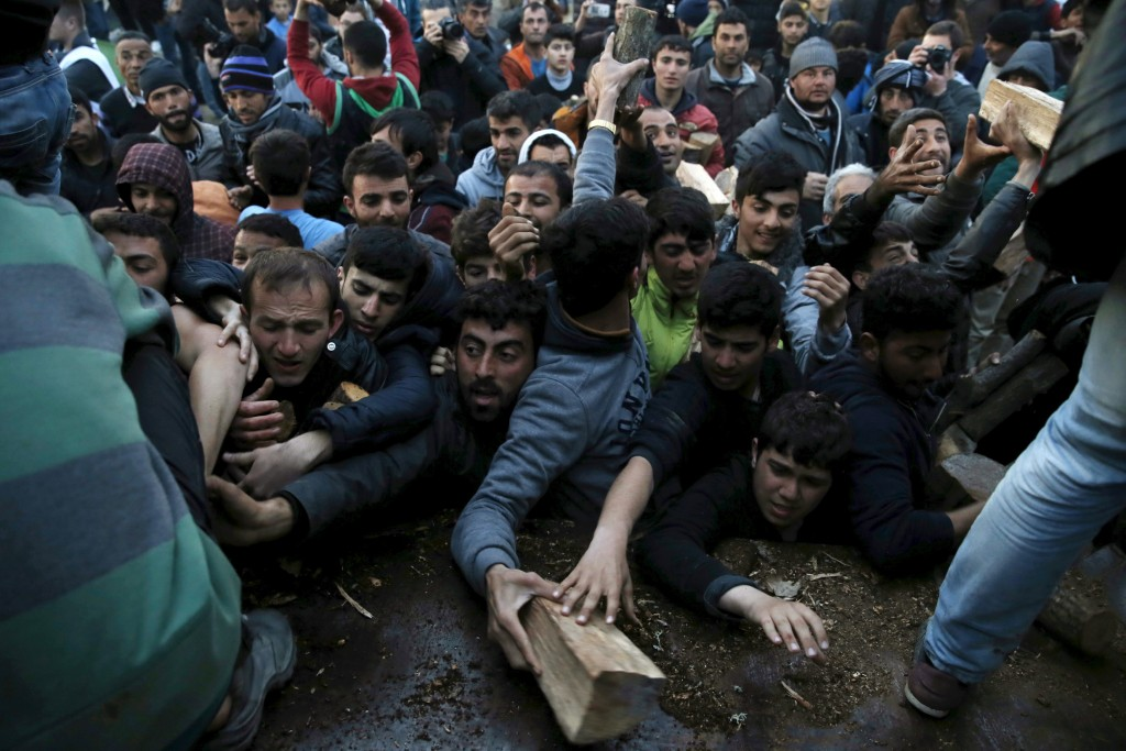 Migrants who are waiting to cross the Greek-Macedonian border scuffle to get a shipment of firewood near the village of Idomeni, Greece March 6, 2016. Marko Djurica/Reuters