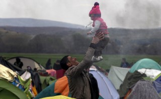 A migrant plays with a baby at a makeshift camp for refugees and migrants waiting to cross the Greek-Macedonian border, near the village of Idomeni, Greece March 6, 2016. Alexandros Avramidis/Reuters