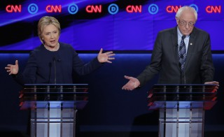 Democratic U.S. presidential candidate Hillary Clinton and rival Bernie Sanders speak simultaneously during the Democratic U.S. presidential candidates' debate in Flint, MichiganMarch 6, 2016. REUTERS/Jim Young  TPX IMAGES OF THE DAY - RTS9KY6