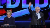 Democratic U.S. presidential candidate Bernie Sanders (R) waves to the crowd as his rival Hillary Clinton gathers her papers at the conclusion of the Democratic U.S. presidential candidates' debate in Flint, Michigan, March 6, 2016. REUTERS/Jim Young  - RTS9L21