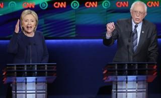 Democratic U.S. presidential candidate Hillary Clinton and rival Bernie Sanders speak simultaneously during the Democratic U.S. presidential candidates' debate in Flint, Michigan, March 6, 2016. Photo by Jim Young/REUTERS