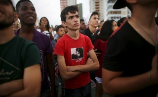"A boy wearing a T-shirt with the image of Cuban revolutionary Ernesto ""Che"" Guevara watches a performance by U.S. electronic group Major Lazer in Cuba's capital Havana on March 6. Photo by Alexandre Meneghini/Reuters"