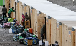 Migrants and refugees arrive in a refugee camp with wood humanitarian-standard shelters in Grande-Synthe, near Dunkerque, northern France, March 7, 2016.   REUTERS/Pascal Rossignol  - RTS9NSI