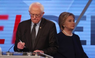 Democratic presidential candidate Sen. Bernie Sanders writes some notes as his rival Hillary Clinton walks behind him to her podium during a commercial break at the Univision News and Washington Post Democratic debate in Kendall, Florida, on March 9. Photo by Carlo Allegri/Reuters