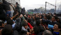 Migrants scuffle as they try to get products from a truck, at a makeshift camp on the Greek-Macedonian border near the village of Idomeni, Greece March 10, 2016. REUTERS/Stoyan Nenov - RTSA8JX