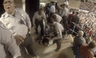 Rakeem Jones lies on the ground while being removed by deputies from a Donald Trump rally in Fayetteville, North Carolina, in a still image from video provided by Ronnie Rouse. Jones was assaulted during his eviction from the rally, and John Franklin McGraw, of Linden, North Carolina, faces criminal charges in the altercation. Photo provided by Ronnie Rouse/Handout via Reuters