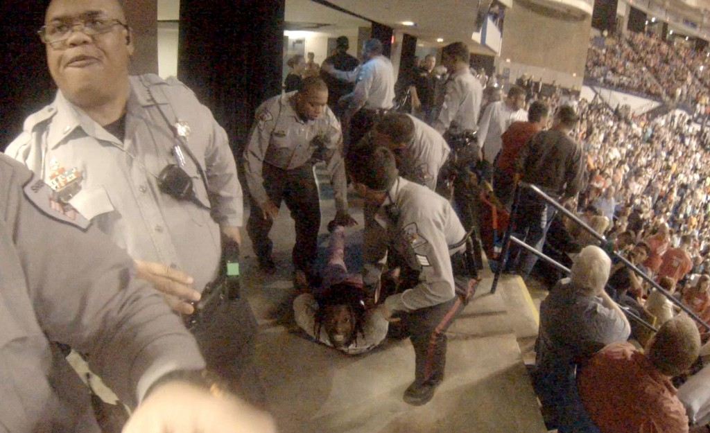 Rakeem Jones lies on the ground while being removed by deputies from a Donald Trump rally in Fayetteville, North Carolina March 9, 2016, in a still image from video provided by Ronnie Rouse March 10, 2016.  Jones was assaulted during his eviction from the rally, and a man faces criminal charges in the altercation. Photo by Ronnie C/Reuters