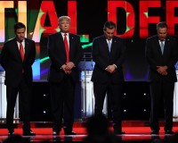Republican U.S. presidential candidate Donald Trump (2nd from L) looks up as rival candidates Marco Rubio (L), Ted Cruz and John Kasich (R) bow their heads for a moment of silence for former first lady Nancy Reagan at the start of  the Republican U.S. presidential candidates debate sponsored by CNN at the University of Miami in Miami, Florida March 10, 2016. REUTERS/Carlo Allegri - RTSAA1J