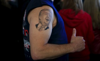 A supporter shows his tattoo before U.S. Republican presidential candidate Donald Trump's campaign rally at Winner Aviation in Youngstown, Ohio  March 14, 2016.  REUTERS/Aaron P. Bernstein - RTSAFR5