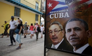 "Tourists pass by images of U.S. President Barack Obama and Cuban President Raul Castro in a banner that reads ""Welcome to Cuba"" at the entrance of a restaurant in downtown Havana, March 17, 2016. Photo by Alexandre Meneghini/Reuters."