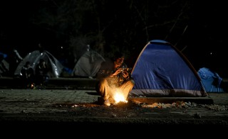 A Pakistani migrant looks at his phone next to railway tracks at a makeshift camp at the Greek-Macedonian border, near the village of Idomeni, Greece March 16, 2016. Picture taken March 16. REUTERS/Alkis Konstantinidis - RTSB8W1