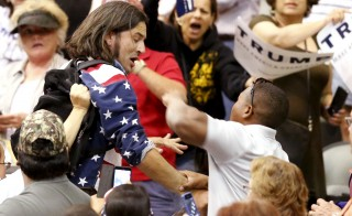A member of the audience (R) throws a punch at a protester as Republican Presidential candidate Donald Trump speaks during a campaign event in Tucson, Arizona. Photo by Sam Mircovich/Reuters