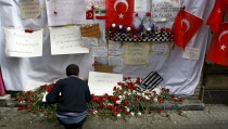 A man places carnations at the scene of a suicide bombing at Istiklal street, a major shopping and tourist district, in central Istanbul, Turkey March 20, 2016. REUTERS/Osman Orsal      TPX IMAGES OF THE DAY      - RTSBBXH