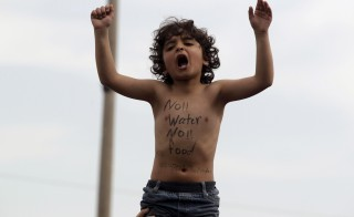 A refugee boy shouts slogans as refugees and migrants protest to demand for the opening of the Greek-Macedonian border, in a makeshift camp near the village of Idomeni, Greece, March 21, 2016. REUTERS/Alexandros Avramidis - RTSBJ6K