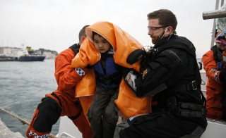 A refugee boy, rescued at open sea, is helped to disembark a Frontex patrol vessel at the port of Mytilene on the Lesbos island, Greece March 22, 2016. REUTERS/Alkis Konstantinidis - RTSBKW8