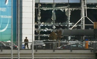 A soldier stands near broken windows after explosions at Zaventem airport near Brussels, Belgium. Photo by Francois Lenoir/Reuters