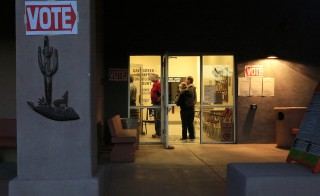 Early morning voters stand in line before sunrise to vote in Arizona's U.S. presidential primary election at a polling station in Cave Creek, Arizona. Photo by Nancy Wiechec/Reuters