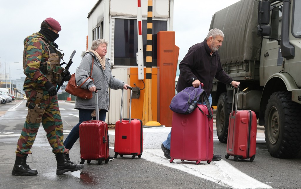 A Belgian soldier accompanies passengers at Brussels' Zaventem airport following Tuesday's bomb attacks in in Belgium on March 23. Photo by Charles Platiau/Reuters