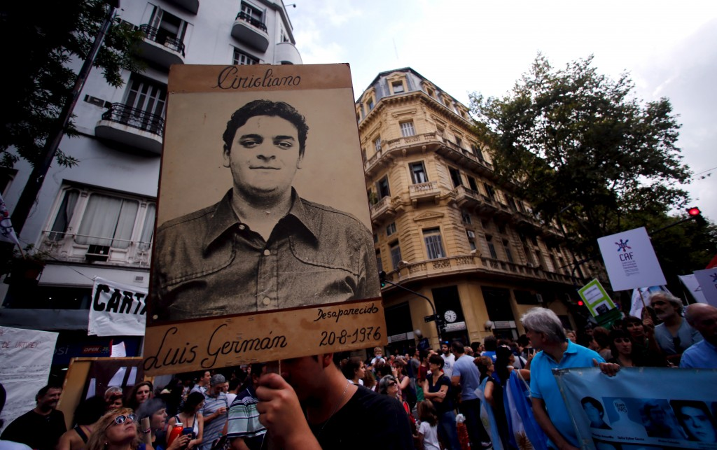 A man holds up a portrait of Luis German Cirigliano, who disappeared during Argentina's 'Dirty war', during a demonstration to commemorate the 40th anniversary of the 1976 military coup in Buenos Aires, March 24, 2016. Photo by Marcos Brindicci/Reuters