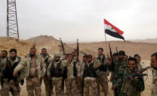 Forces loyal to Syria's President Bashar al-Assad flash victory signs and carry a Syrian national flag on the edge of the historic city of Palmyra in Homs Governorate, in this handout picture provided by SANA on March 26, 2016. On Sunday, the Syrian government was able to retake the ancient city after  Islamic State fighters wrested control of the Palmyra in May last year. Sana/Reuters
