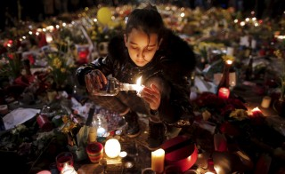 A girl lights candles as people pay tribute to the victims of Tuesday's bomb attacks, at the Place de la Bourse in Brussels, Belgium, March 26, 2016. REUTERS/Christian Hartmann      TPX IMAGES OF THE DAY      - RTSCCP0
