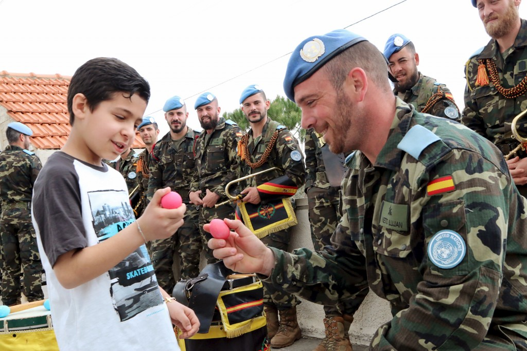 A Spanish member of the United Nations Interim Forces (UNIFIL) breaks his egg with a Lebanese boy after an Easter service in Marjayoun village, southern Lebanon March 27, 2016. REUTERS/Karamallah Daher  - RTSCE71