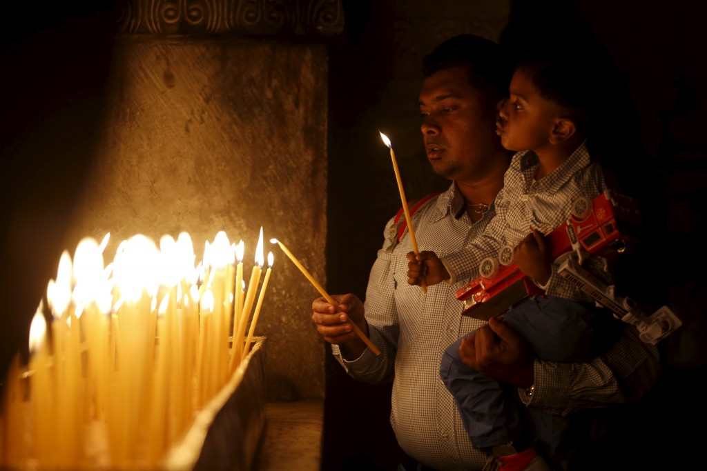 A boy lights a candle with his father during Easter Sunday mass at the Church of the Holy Sepulchre in Jerusalem's Old City March 27, 2016. REUTERS/Amir Cohen  - RTSCE8U