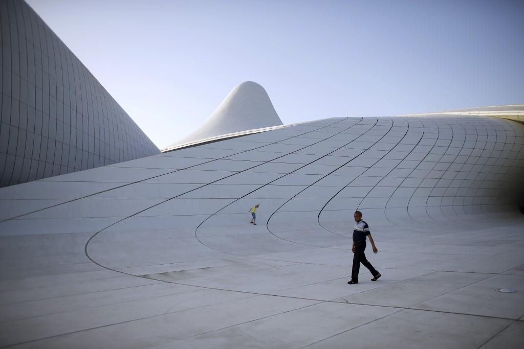A man and a boy walk outside the Heydar Aliyev Center, ahead of the European Games in Baku, Azerbaijan, June 11, 2015. REUTERS/Stoyan Nenov  - RTX1G463