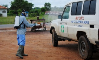 A health worker sprays disinfectant on an ambulance in Nedowein, Liberia, July 15, 2015. A Liberian woman has died of Ebola in a hospital in Monrovia shortly after being admitted, becoming the sixth confirmed case and second death since the virus resurfaced last month, a senior medical official said on Tuesday. REUTERS/James Giahyue  - RTX1KE1L