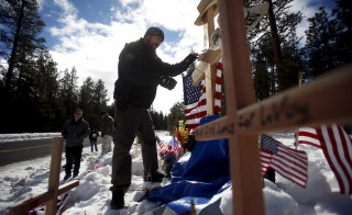 Members of the Pacific Patriots Network visit a memorial for Robert 'LaVoy' Finicum where he was shot and killed by law enforcement on a highway north of Burns, Oregon January 31, 2016. The FBI negotiated with four armed occupants at the remote Malheur National Wildlife Refuge in Oregon on Saturday while the holdouts in a video posted online expressed their mistrust of the government and reluctance to leave. REUTERS/Jim Urquhart - RTX24U6B