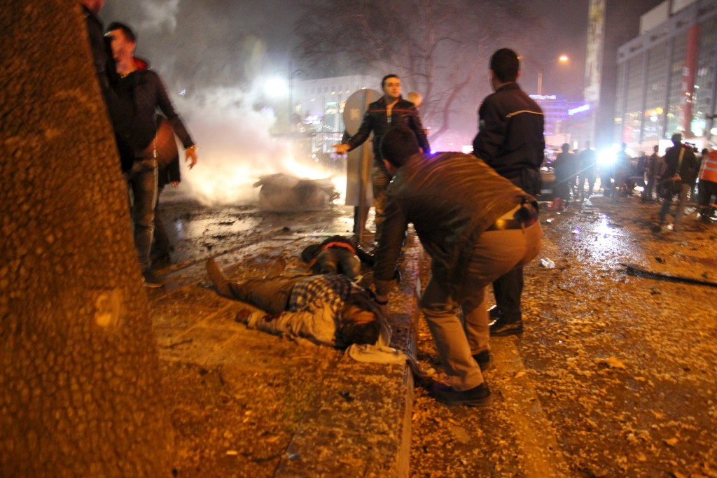 People help an injured person on the ground near the explosion site in Ankara, Turkey March 13, 2016. Tumay Berkin/Reuters