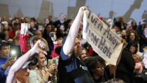 Protesters hold up signs as U.S. Republican presidential candidate Donald Trump speaks at a town hall campaign event in Hickory, North Carolina. March 14, 2016. REUTERS/Chris Keane  - RTX294NA