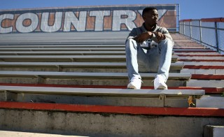 James Turner, a freshman at Florida State University and a foster youth, sits on the bleachers at his former high school in Orlando, Fla.  Photo by Mike Fritz