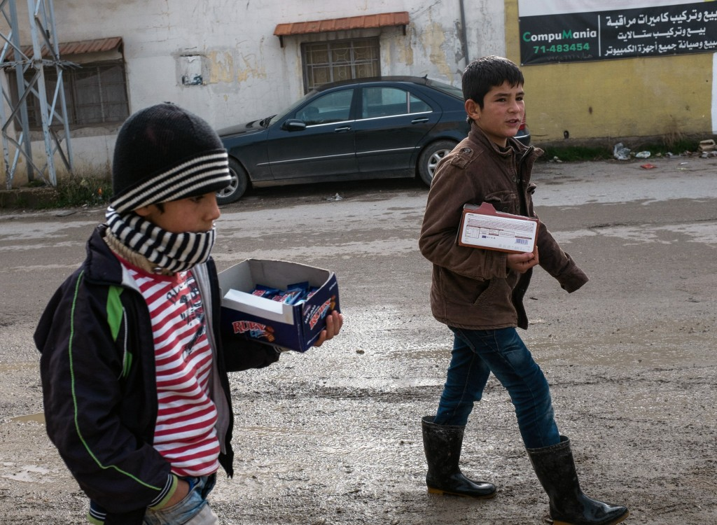 Two brothers sell candy bars in Barelias, Lebanon, to try to earn some income for their family on Jan. 22. Photo by Christopher Lee for The GroundTruth Project