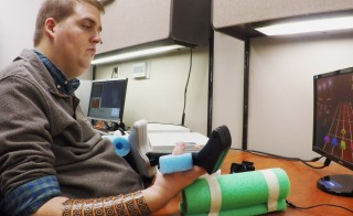 Ian Burkhart, 24, plays a guitar video game as part of a study into neural bypass technology that allowed him to regain functional use of his paralyzed hand. Photo by Ohio State University Wexner Medical Center/ Batelle