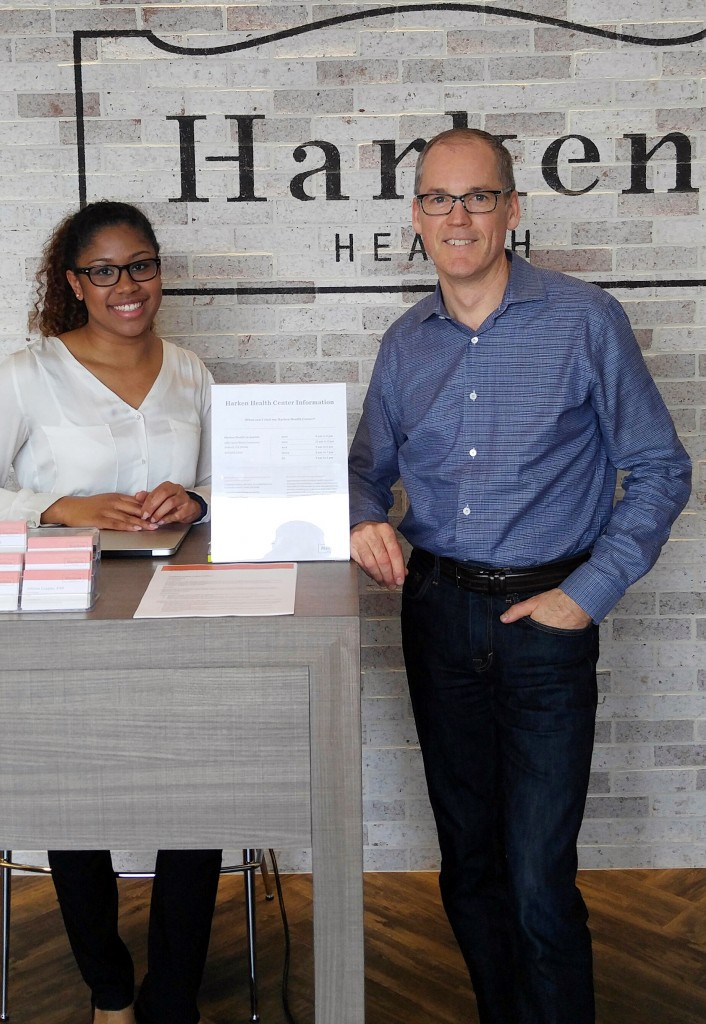 Tom Vanderheyden, CEO OF Harken Health, stands with a greeter at the