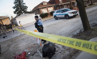 A Chicago police officer guards the perimeter of a crime scene where six people were found slain inside a home on the city's Southwest Side on February 4, 2016 in Chicago, Illinois. Scott Olson/Getty Images