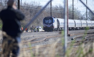 CHESTER, PA - APRIL 3:  A man observes the crash site of Amtrak Palmetto train 89 on April 3, 2016 in Chester, Pennsylvania.  Two people are confirmed dead after the lead engine of the train struck a backhoe that was on the track south of Philadelphia, according to published reports. Approximately 341 passengers and seven crew members were onboard the train, which was traveling from New York to Savannah, according to Amtrak.  (Photo by Mark Makela/Getty Images)