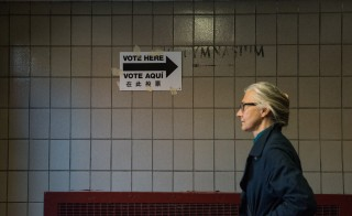 A woman walks past a voting sign at Public School 22 on April 19, 2016 in the Brooklyn borough of New York City. Voters went to the polls in New York for the presidential primary election on April 19, 2016. About 126,000 people were taken off the voter rolls and the New York City Board of Elections chief Brooklyn clerk was suspended.  Stephanie Keith/Getty Images