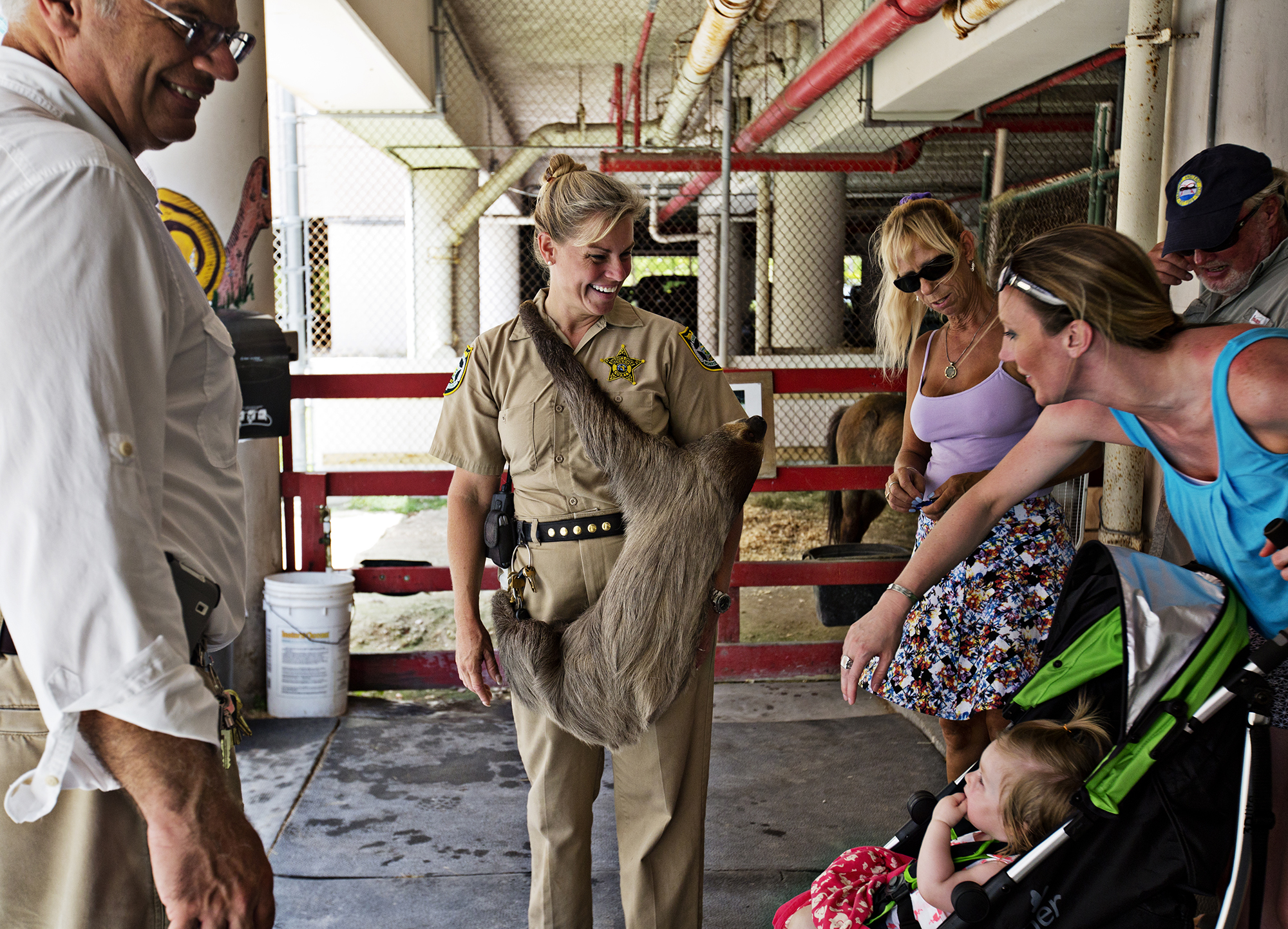 """Curator Jeanne Selander - """"Farmer Jeanne"""" - holds """"Mo"""" the sloth, and visits with a crowd of visitors for an open house at the jail farm. """"Everyone thinks he is hugging me, but really he just thinks I'm a tree,"""" says Selander.  Photo by Kim Raff"""